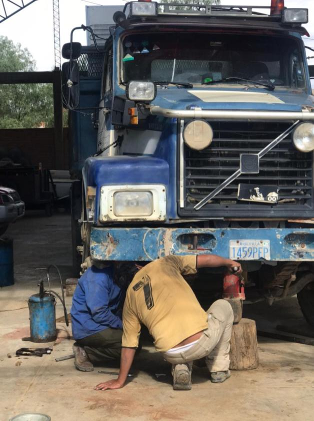 Mano a Mano mechanics repairing a dump truck.