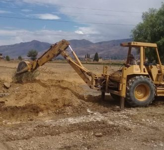 Backhoe building a water holding pond
