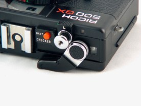 "The Ricoh 500GX's blisters. On the right of the ""L"" lever, the good idea: a cocked shutter indicator."