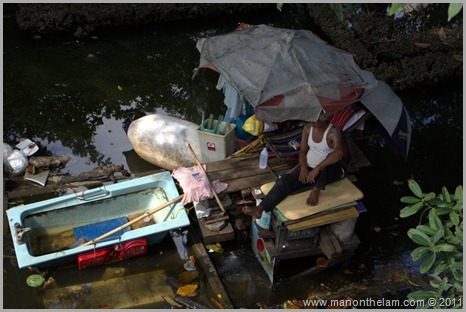Man on raft in flooded district of Bangkok Thailand Best of Travel 2011 Photo