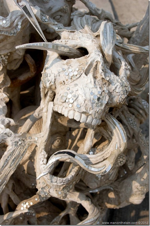 Skull with snake through eye socket -- White Temple, Chiang Rai, Thailand