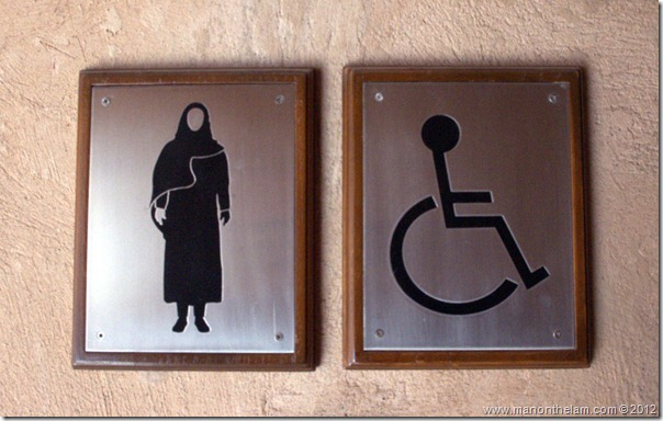 Offbeat Images -- Middle Eastern woman wearing abaya toilet sign, Nizwa Fort, Nizwa, Oman