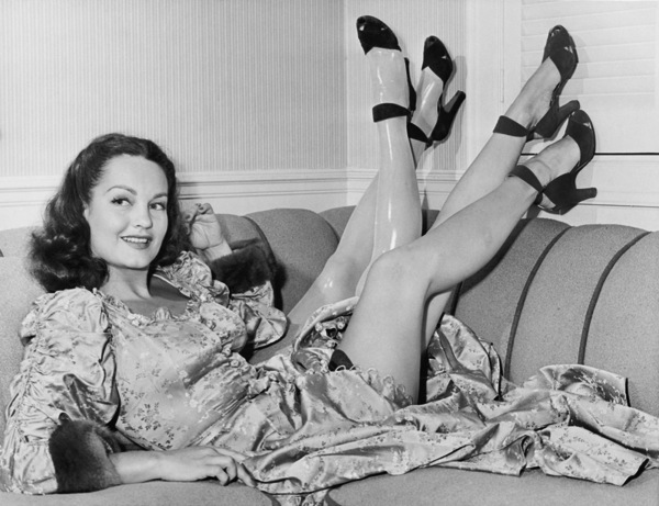 Woman on couch with fake prosthetic legs in high heels black and white