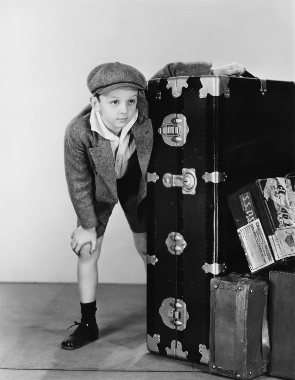 Boy with suitcases black and white