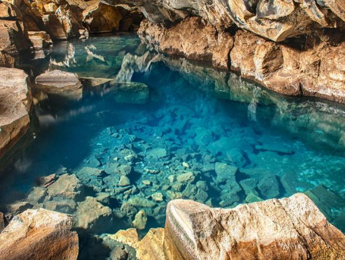 Vulcanic cave with blue thermal water near Myvatn.jpg