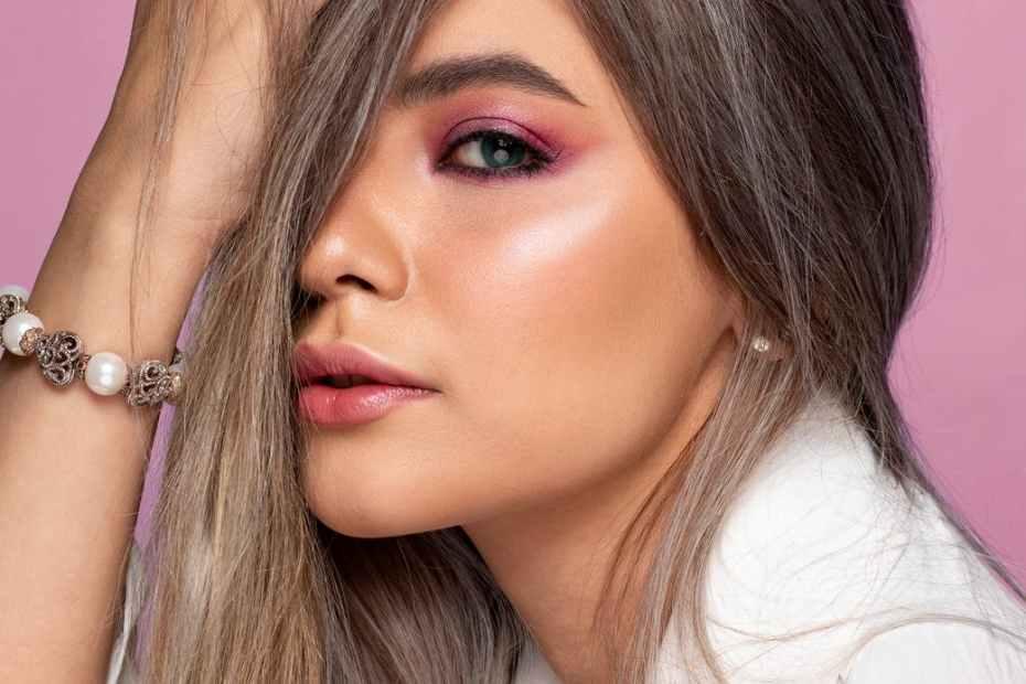 stylish model touching hair on pink background