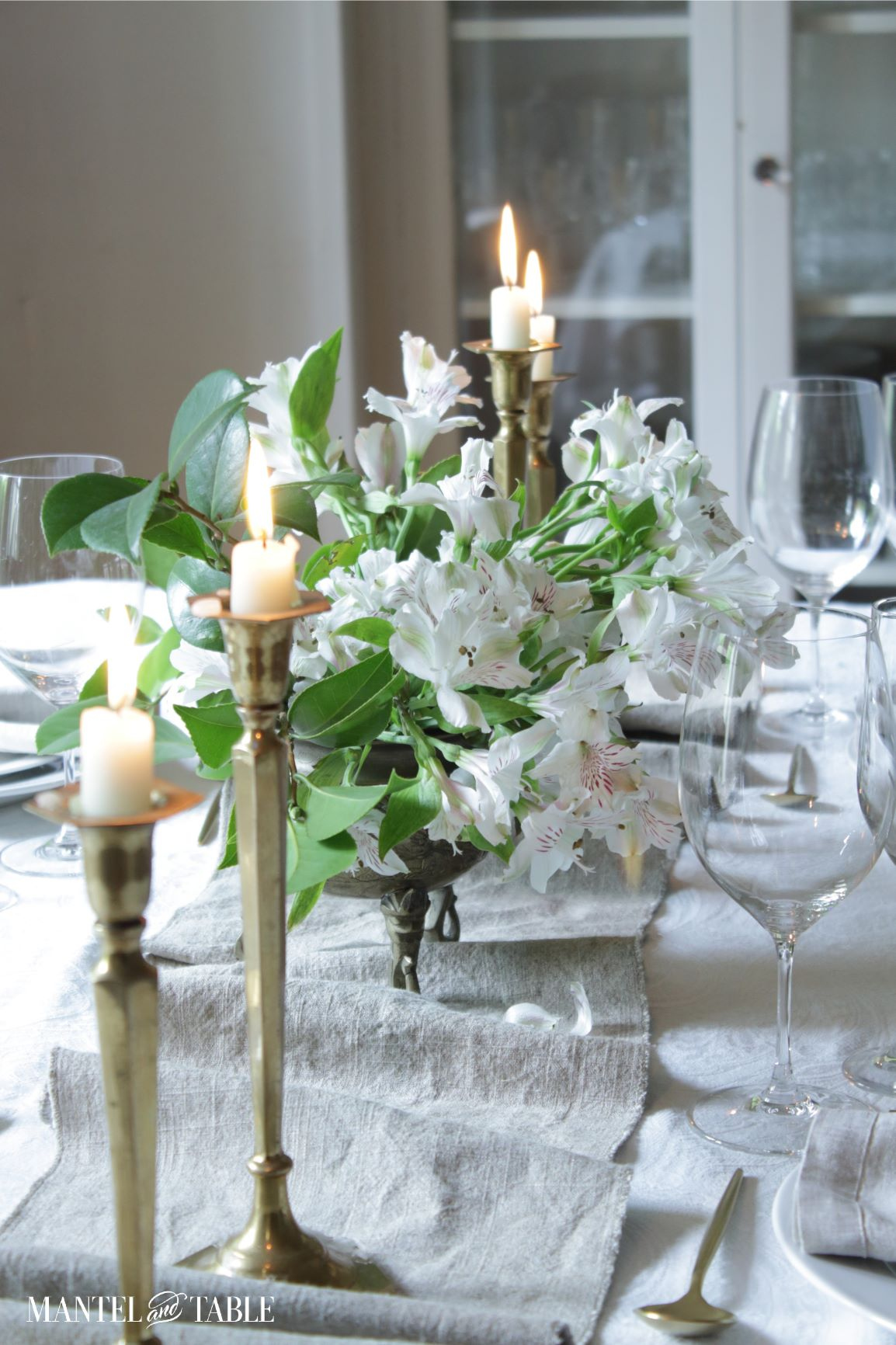 Linen table runner on table with white flowers, candles