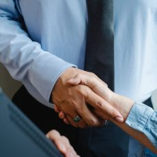 anonymous colleagues shaking hands before business meeting