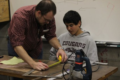 Mr. Eric Allgeier (YPAS Design and Production) helps a student measure wood the will be used in the set.