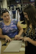 Sara Redden (12) instructs Reagan Bouchillon (12) on where to cut fabric for a costume that will be used in the YPAS performance of Macbeth.