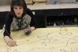 Gabrielle Lindley (12) paints the finishing touches on the map for Macbeth.