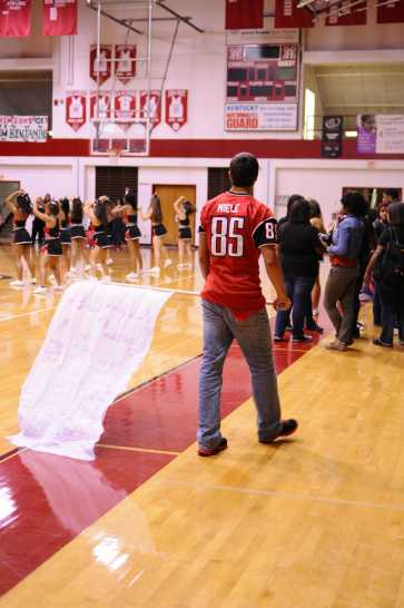 Chris Miele(12), football team captain, awaits for the seniors to enter as he holds one of the many flags with spirit slogans written on them. Photo by Jack Steele.