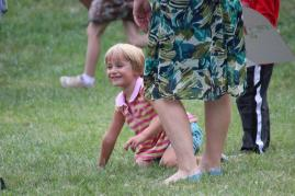 Children play tag with parents in an open field.