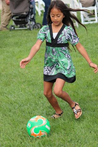 While parents watch the live concert, children kick around a soccer ball.