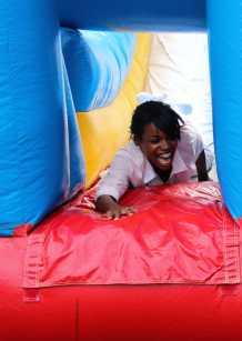 Margo Demus (11) slides down the blowup slide winning the race. Photo by Mesa Serikali