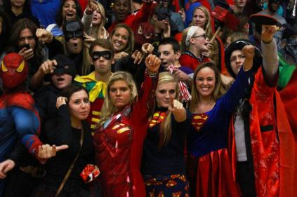 Allison Bray (11), Callie Kidwell (11), Annie Roth (11), and others strike a super-hero pose as the junior class packs into the gym. Photo by Meg Shanks