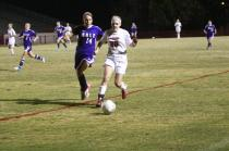 Devin Spratt (10) dribbles the ball towards the sideline trying to keep the opposing Male player from stealing it away.