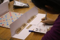 Sherry Wang (10) fills out the score sheet before the Cal v. Manual French Scrabble game. Photo by Mai Nguyen.