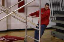 Graham Manuel, (12) slides the ladder across the floor and makes sure he doesn't run into the bleachers.
