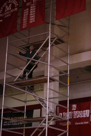 Bo, the Janitor, helps to take down one of the banners.
