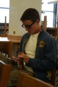 John King (12) waits for the presentation to start, passing time by beening on his phone.