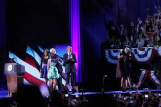 Vice President Joe Biden shares a celebratory hug with President Obama's daughters, Malia (left) and Natasha (right) while Jill Biden and First Lady Michelle Obama embrace one another on the stage of McCormick Place before the thousands of rally attendees following President Obama's speech.