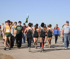 The girls' team jogs towards the finish line to congratulate the boys on their finish.