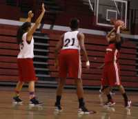 Erika Hawkins looks for a teammate to pass the ball to while being guarded by Mackinley Poole and Jaeda Coffey