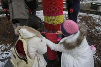 Students measure yarn pieces before attaching them to a tree. Photo by Allison Traylor.