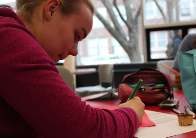 Brigette Schuman (11) concentrates on the card that she is making for a charity.