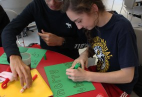 Jay Kumar (11) and Holly Smith (11) help each other think of designs for their cards. Since it was Key Club Week, Smith also wore her Key Club t-shirt to get an additional hour.