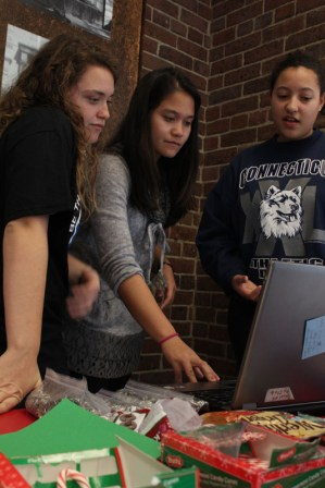 At the meeting before the service project, Key Club president Jade Glore (12) helps members Melissa Nadeau (12) and Kyla Grant (11) check their hours.