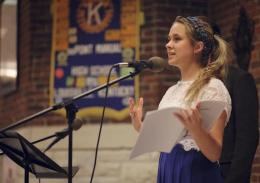 "Co-Editor in Chief of One Blue Wall, Sadie Birchfield (12) introduces the audience to last year's issue of Manual's literary magazine, ""Plethora"" and encourages the audience to purchase a copy before introducing them to the first students to read."