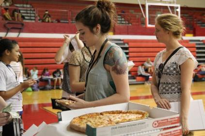 Gwendolyn Heine (12) bought pizza while she was getting her yearbook. Photo by Mai Nguyen.