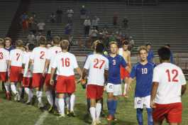 The Crimsons shake hands with their victorious opponents after the game
