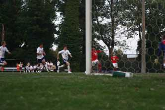 Greg Healey (12, #13) takes a shot but misses the goal