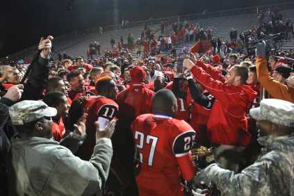 The entire football team and the coaches cheer with the barrel in their hands.