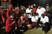 All of the coaches pose for a picture with the barrel after their victory
