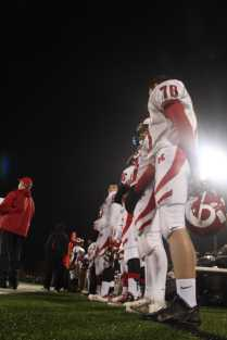 Manual football players stand in the rain watching from the sidelines as Trinity scores again.