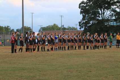 The varsity team lined up for the playing of the national anthem.