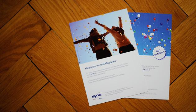 Syna – Beitragsbild mit zwei Flyer