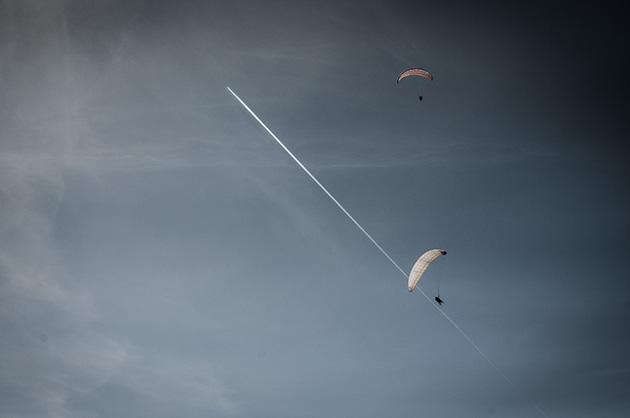 Fotografie – mehrere Gleitschirme am Himmel mit einem Kondensstreifen eines Flugzeuges im Hintergrund.
