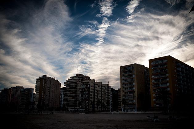 Wohnblocks am Strand von Cullera in der Abenddämmerung. Im oberen Bildbereich Wolkenzeichnungen.