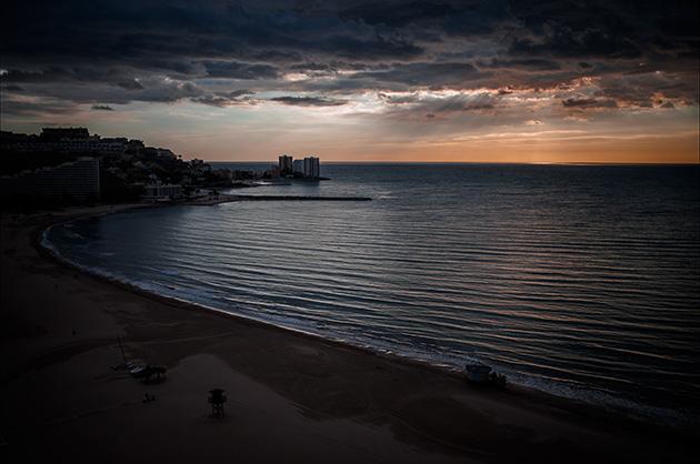 Fotografie von einem Hotelblock und der Bucht von Cullera kurz nach dem Sonnenaufgang.