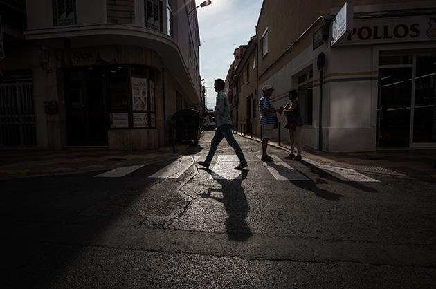 Alter Dorfteil von Cullera, Spanien. Ein Mann läuft im Gegenlicht über einen Fussgängerstreifen. Nikon D810, 20mm/1.8