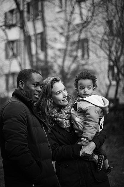 Familie, Mann, Frau und Kind in einem Garten an der berner Gruberstrasse in der stätdischen Wohnbausiedlung Murifeld