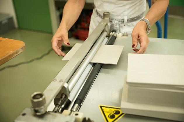 Eine Maschine, die die Graukartondeckel gleichmässig mit Weissleim bestreicht