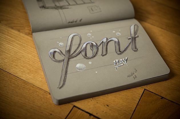 «font» – Schriftzeichnung mit schwarzem und blauem Kugeschreiber und Weiss-Stift auf grauem Papier