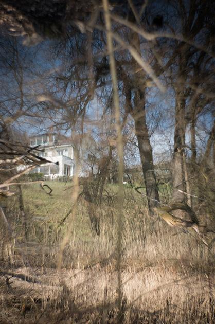 Spieglein Spieglein auf dem Wasser. Reflexion eines Hauses in einem Aare-Weiher. Aufgenommen mit einem 85mm Petzval-Objektiv.