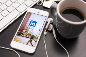 linkedin in cellphone and headset with a cup of coffee